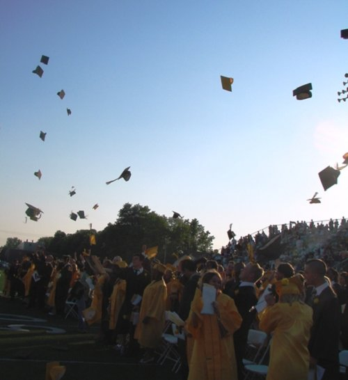The graduates celebrate by throwing their hats in the air!